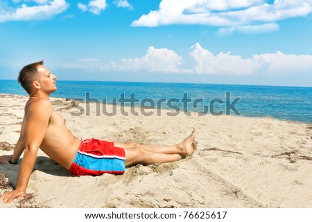 handsome man enjoying in sun on the beach