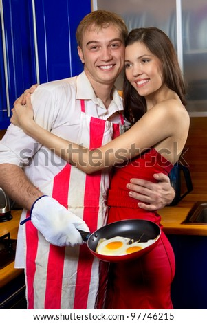 Handsome man frying eggs for his girlfriend in kitchen