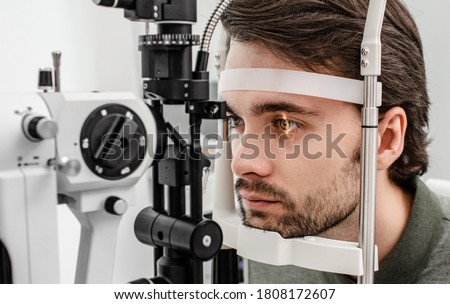 Handsome man getting an eye exam at ophthalmology clinic. Checking retina of a male eye close-up