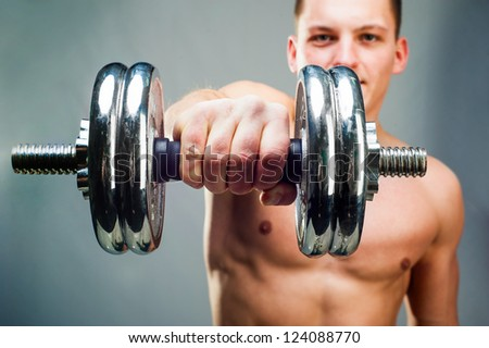 handsome man holding a dumbbell in front