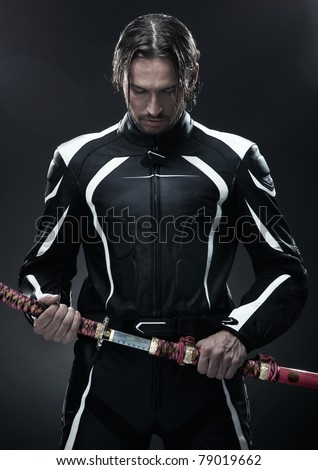 Handsome man holding a samurai sword