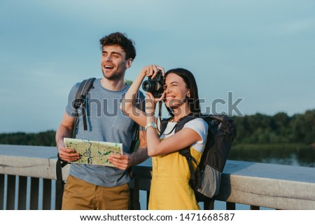 handsome man holding map and asian woman in overalls taking photo