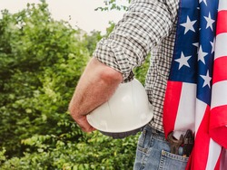 Handsome man holding US Flag and construction helmet against the background of trees, blue sky and sunset. View from the back. Labor and employment concept
