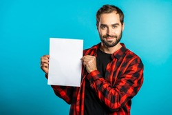 Handsome man holding vertical white a4 paper poster. Copy space. Smiling hipster guy in red plaid shirt on blue background.
