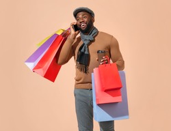 Handsome man holds shopping bags and talks by mobile phone. Photo of african man in stylish casual clothes on beige background.