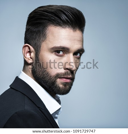 Handsome man in black suit with white shirt  - posing  at studio. Attractive guy with fashion hairstyle.  Confident man with short beard. Adult boy with brown hair.