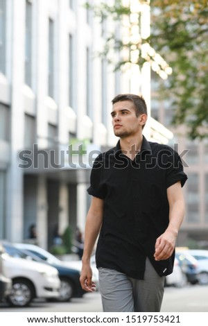 Handsome man in casual casual clothes strolling down the street in the modern city and looking away, wearing a dark shirt.Street style portrait. Fashionable guy walking down the street,photo in motion