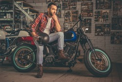 Handsome man in casual clothes is holding a helmet and looking away while sitting on the motorcycle in the repair shop