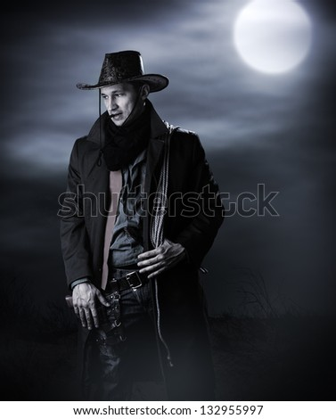 Stock Photo Handsome man in cowboy costume stay in steppe at night with full moon. Vampire Hunter
