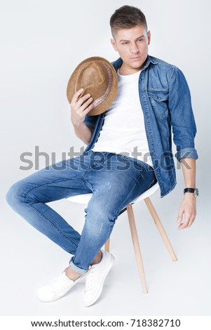 handsome man in denim with hat sits on chair on white background Stok fotoğraf ©