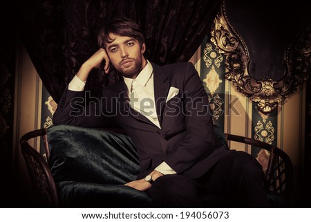 Handsome man in elegant black suit posing in the classical vintage interior.