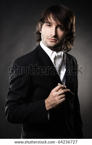 Handsome man in elegant clothing with cigar against black background - stock photo