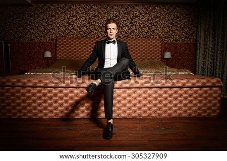 Handsome man in elegant suit sitting on a bed. Luxury. Vintage interior.