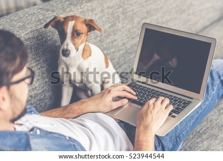 Handsome man in eyeglasses is using a laptop while lying on couch at home. Cute dog is looking at his guardian