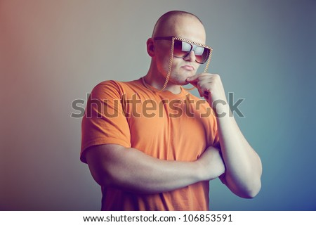 Handsome man in fashionable eyeglasses with chain, studio shot