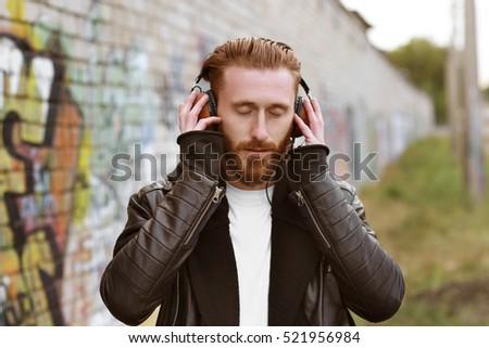 Handsome man in headphones listening to music outdoors #521956984