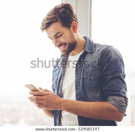 Handsome man in jean clothes is using a smartphone and smiling while standing near the window #529085197