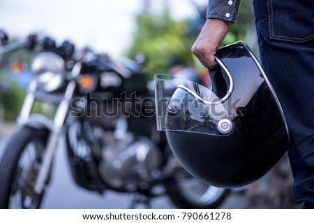 Handsome man in jean is holding a helmet and vintage motorcycle blur background - Shutterstock ID 790661278