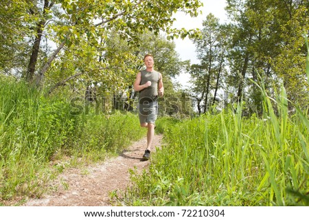 Handsome man in sportswear running in the forest