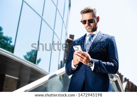 handsome man in suit and glasses using digital device #1472945198