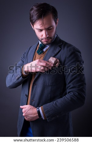 Handsome man in suit with tie and pocket square, fixing his pocket square, on dark gray background