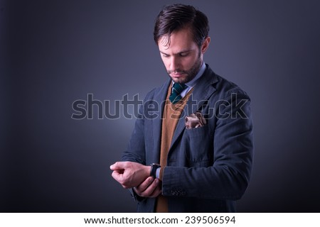 Handsome man in suit with tie and pocket square, looking at his watch, on dark gray background