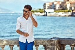 Handsome man in summer outfit wear sunglasses posing outdoor over city view
