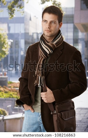 Handsome man in trendy clothes having scarf and bag standing waiting outside of building.