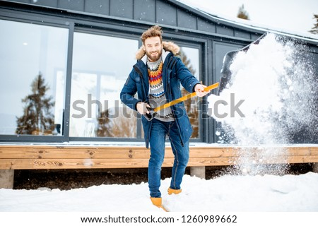 Handsome man in winter clothes cleaning snow with a shovel near the modern house in the mountains