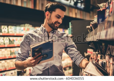 Handsome man is choosing a magazine and smiling while doing shopping at the supermarket