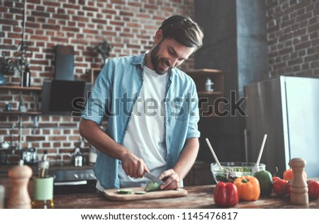 Handsome man is cooking on kitchen and smiling.