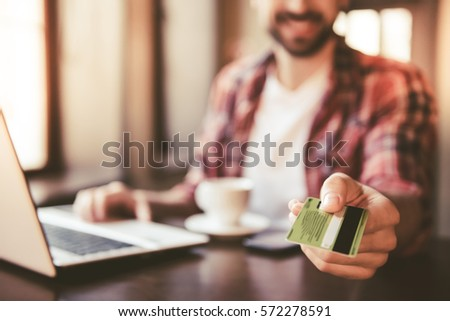 Handsome man is giving a credit card and smiling while working with a laptop in cafe #572278591