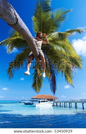 Handsome man is sitting on a palm tree