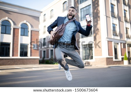 Handsome man jumping. Handsome man jumping after reading approving message from successful company