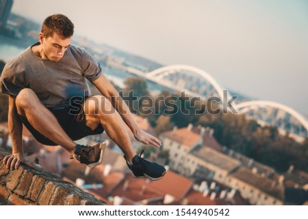 Handsome man jumping over a wall. Free running parkour - Stock photo