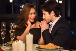 Handsome man kissing hand of his girlfriend in restaurant during romantic dinner