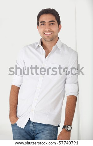 Handsome man leaning against a wall and smiling