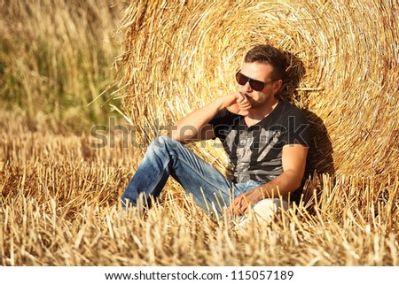 handsome man leaning against golden hay roll