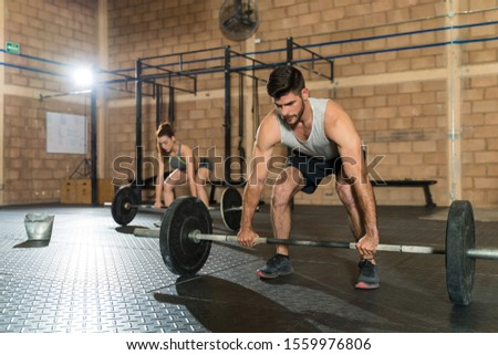 Handsome man lifting barbell in front of young woman during cross training at health club