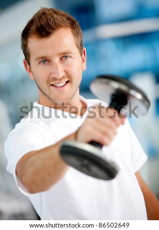 Handsome man lifting free weights at the gym