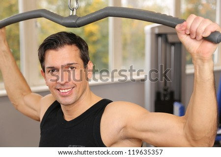 Handsome man lifting weights in a gym