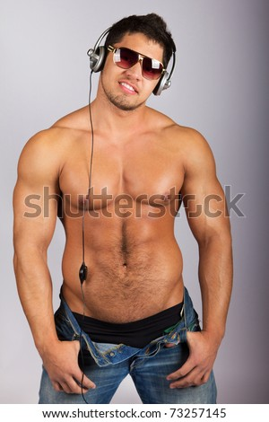 handsome man listening to music on headphone against natural background