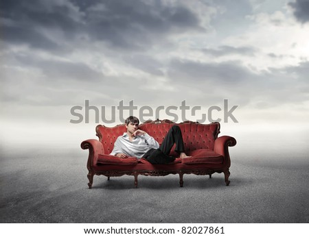 Handsome man lying on a sofa in a desert