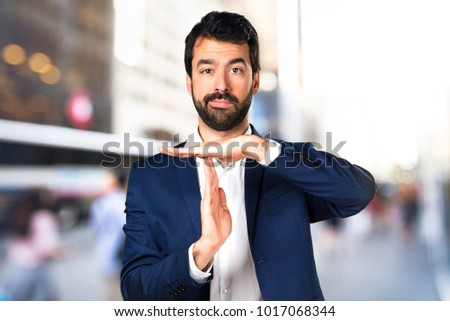 Handsome man making time out gesture on unfocused background