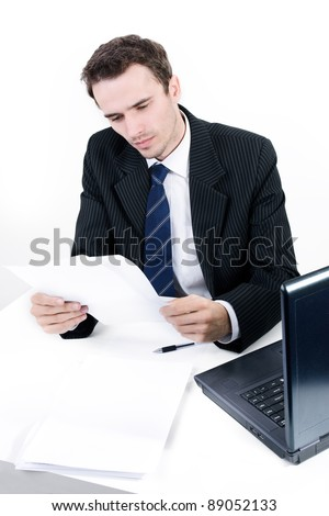 Handsome man, male model as businessman, boss, manager, executive director in suit reading correspondence in office near computer, made in studio on white background