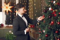 Handsome man near Christmass tree. Gentelman in a black suit.