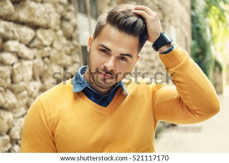 Handsome man near old building with brick wall #521117170