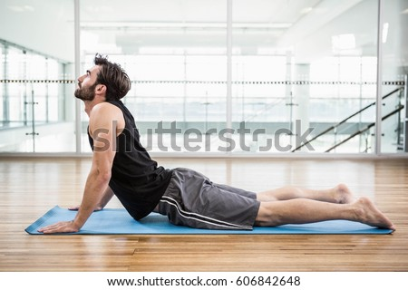 Handsome man on cobra pose on the mat in the studio