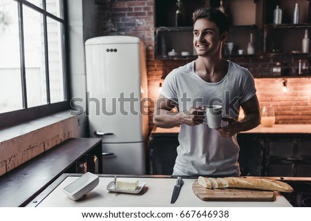 Stock Photo Handsome man on kitchen is smiling and drinking coffee in the morning.