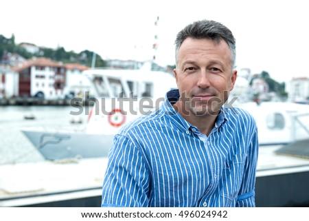 Handsome man. Outdoor male portrait. Middle-aged man posing against ancient european sea port, summer outdoor portrait, image toned. Saint Jean de Luz, France.